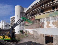 Com retroescavadeira e segurança reforçada, empresa começa a demolir Hotel Reis Magos, em Natal